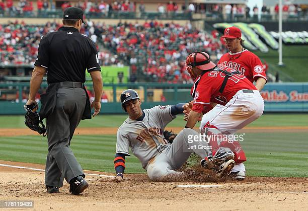 Carlos Pena of the Houston Astros is tagged out at home by catcher Hank Conger of the Los Angeles Angels of Anaheim as pitcher CJ Wilson of the...