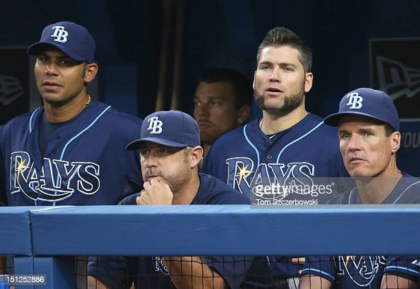 Carlos Pena of the Tampa Bay Rays and hitting coach Derek Shelton and Luke Scott and pitching coach Jim Hickey look on during MLB game action against...