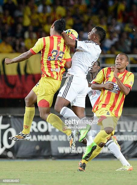 Carlos Peralta of America de Cali jumps for the ball with Eder Castañeda and Eddie Segura of Deportivo Pereira during a match between Deportivo...