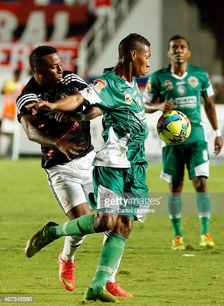 Carlos Peralta of America de Cali struggles for the ball with Aramys Rodríguez of Valledupar during a match between America de Cali and Valledupar as...