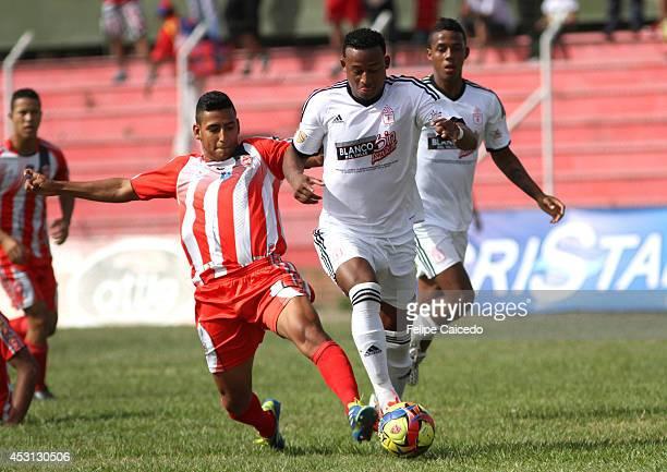 Carlos Peralta of America de Cali struggles for the ball with Emerzon Lazo of Expreso Rojo during a match between America de Cali and Expreso Rojo as...