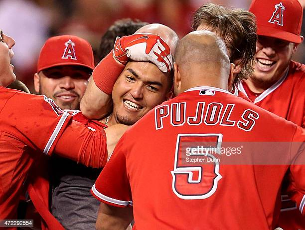 Carlos Perez of the Los Angeles Angels of Anaheim is mobbed by teammates after leading off the ninth inning with a walk off home run to win the game...
