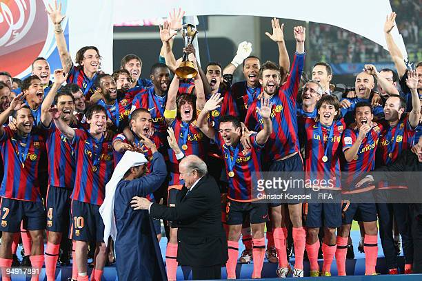 Carlos Puyol holds the cup aloft amongst FC Barcelona players after it was presented by FIFA president Joseph Blatter and Mohammed Khalfan AlRumaithi...