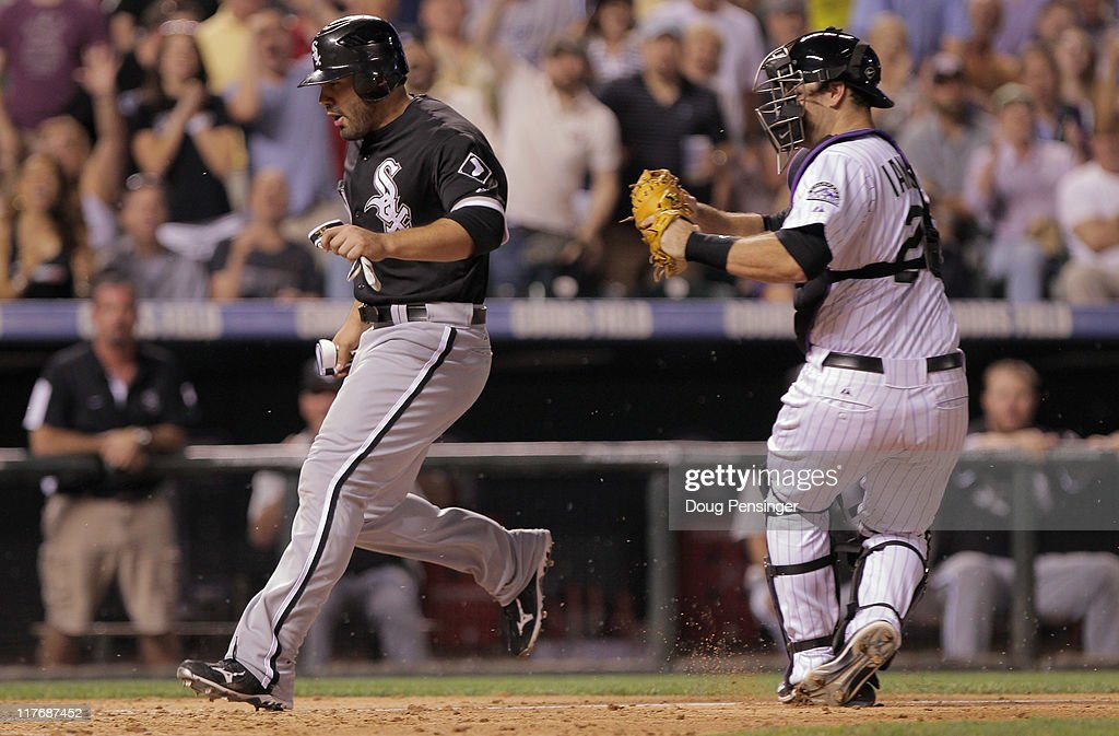 Carlos Quentin #20 of the Chicago White Sox goes around catcher Chris Iannetta #20 of the Colorado Rockies to score the game winning run on a sacrfice fly by A.J. Pierzynski of the White Sox off of relief pitcher Huston Street of the Rockies in the ninth inning during Interleague play at Coors Field on June 29, 2011 in Denver, Colorado. The White Sox defeated the Rockies 3-2.
