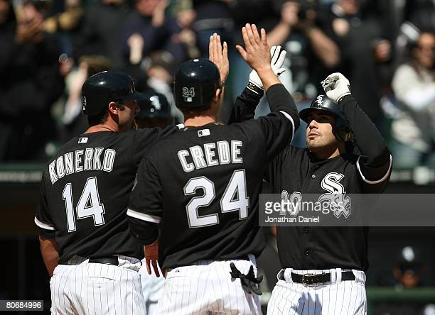 Carlos Quentin of the Chicago White Sox is greeted by teammates Joe Crede and Paul Konerko after hitting a threerun home run in the fourth inning...