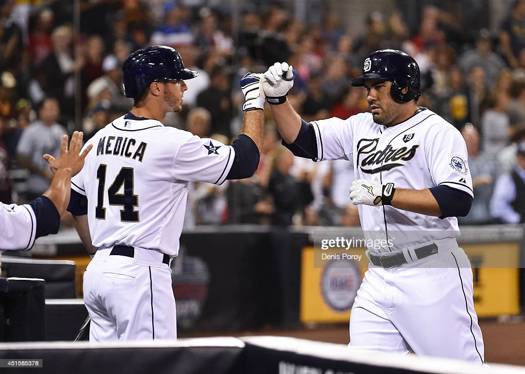 Carlos Quentin #18 of the San Diego Padres is congratulated by Tommy Medica #14 after hitting a two-run home run during the seventh inning of a baseball game against the Cincinnati Reds at Petco Park July 1, 2014 in San Diego, California.