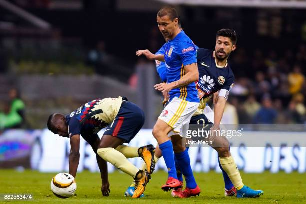 Carlos Quintero and Oribe Peralta of America fight for the ball with Jesus Duenas of Tigres during the semifinal first leg match between America and...