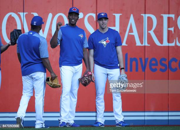 Carlos Ramirez of the Toronto Blue Jays and Aaron Sanchez look on from left field during batting practice before the start of MLB game action against...