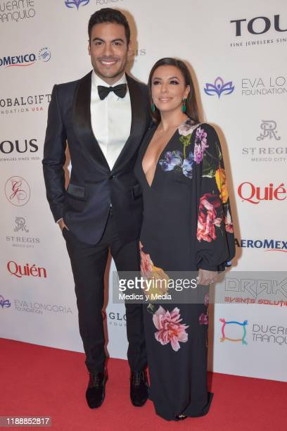 Carlos Rivera and Eva Longoria pose for photos during a red carpet of the The Global Gift Foundation gala at Hotel St. Regis on November 19, 2019 in...
