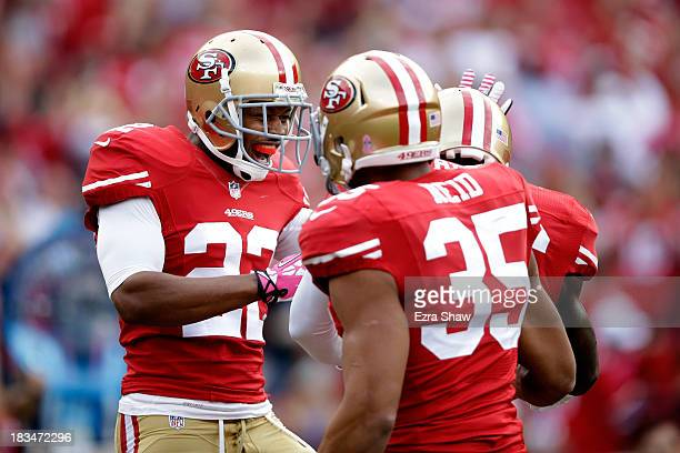 Carlos Rogers and Eric Reid celebrate a touchdown scored by Tramaine Brock of the San Francisco 49ers off of an interception by Matt Schaub of the...