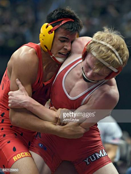 Carlos Romo of Rocky Ford tries to pull down Spencer Holtorf of Yuma by the arm during their 2A 138 pound match in the Colorado high school state...