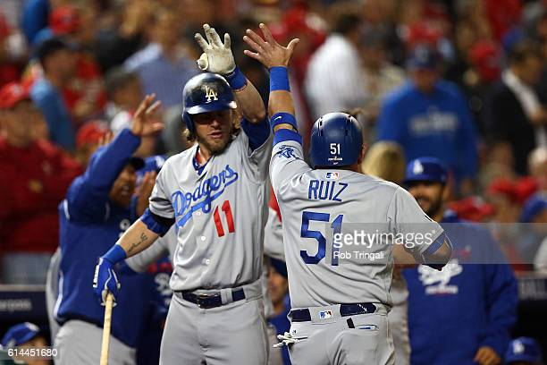 Carlos Ruiz is congratulated by Josh Reddick of the Los Angeles Dodgers after scoring during Game 5 of NLDS against the Washington Nationals at...