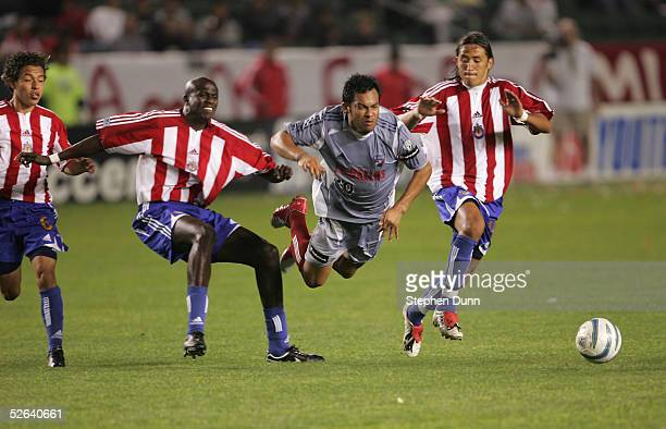 Carlos Ruiz of FC Dallas is upended between Ezra Hendrickson, who received a yellow card for the play, and Hector Cuadros of Chivas USA on April 16,...