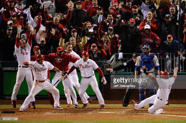 Carlos Ruiz of the Philadelphia Phillies celebrates with his teammates as he slides safely into home as he scores the winning run on a walkoff 2-run...