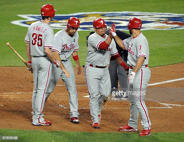 Carlos Ruiz of the Philadelphia Phillies gets congratulated by teammates Pedro Feliz Cole Hamels and Raul Ibanez after Ruiz hit a three run home run...