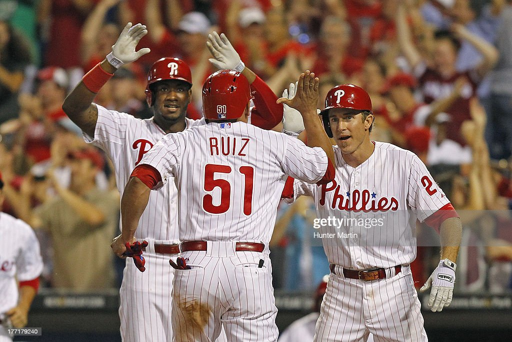 Carlos Ruiz #51 of the Philadelphia Phillies is greeted at home plate by Domonic Brown #9 (L) and Chase Utley #26 (R) as he scores the winning run in the ninth inning during a game against the Colorado Rockies at Citizens Bank Park on August 21, 2013 in Philadelphia, Pennsylvania. The Phillies won 4-3.