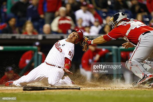 Carlos Ruiz of the Philadelphia Phillies is tagged out by catcher Wilson Ramos of the Washington Nationals while trying to score on a fielders choice...