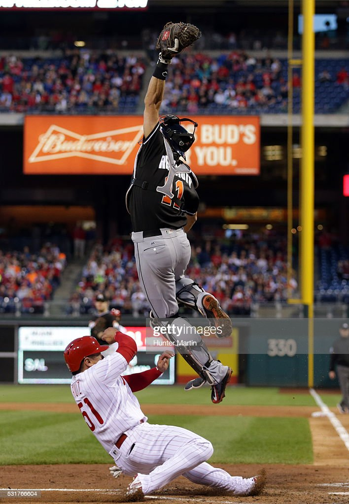 Carlos Ruiz #51 of the Philadelphia Phillies slides safely into home as J.T. Realmuto #11 of the Miami Marlins leaps to catch the throw in the fourth inning during a game at Citizens Bank Park on May 16, 2016 in Philadelphia, Pennsylvania.