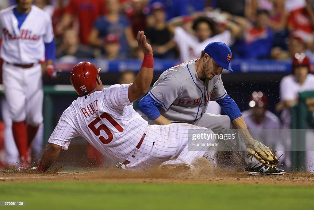 Carlos Ruiz #51 of the Philadelphia Phillies slides safely into home plate as Erik Goeddel #62 of the New York Mets attempts to make the tag in the eighth inning during a game at Citizens Bank Park on July 16, 2016 in Philadelphia, Pennsylvania. The Phillies won 4-2.
