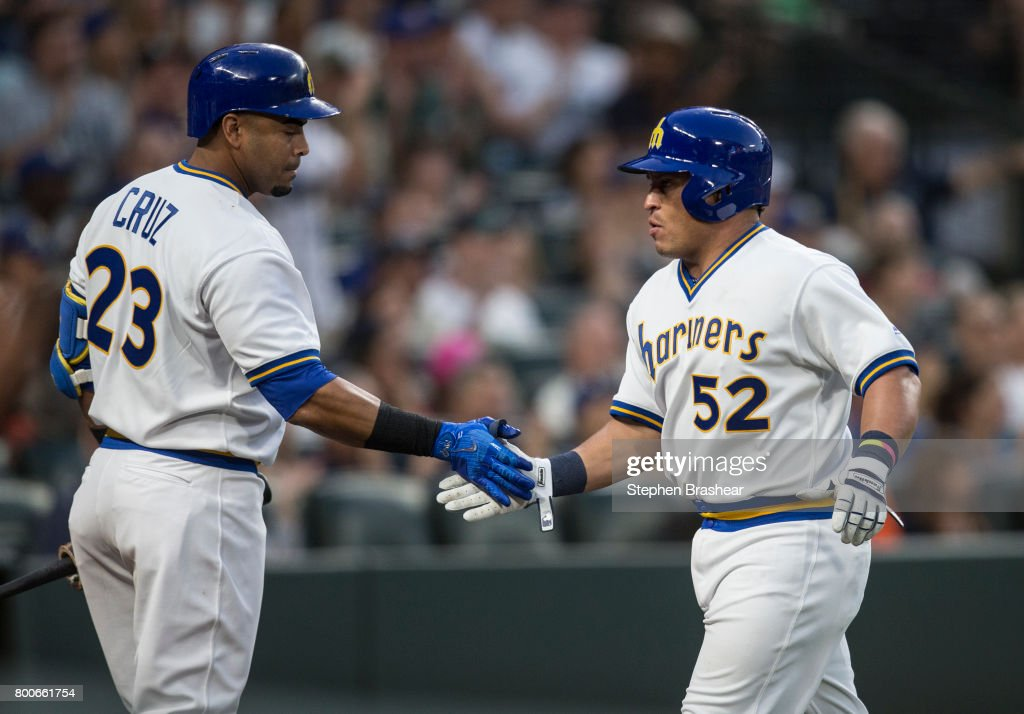 Carlos Ruiz #52 of the Seattle Mariners is congratulated by Nelson Cruz #23 of the Seattle Mariners after scoring a run on a a RBI-single by Robinson Cano #22 of the Seattle Mariners off of relief pitcher Will Harris #36 of the Houston Astros during the sixth inning of a game at Safeco Field on June 24, 2017 in Seattle, Washington.