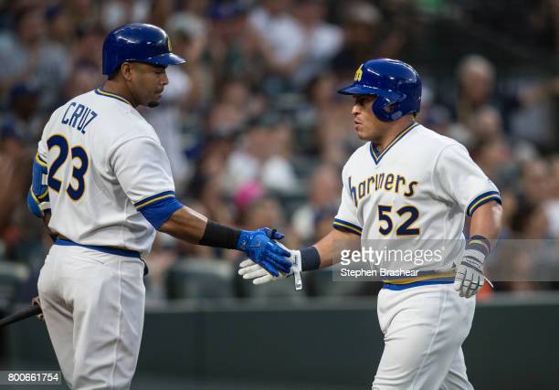 Carlos Ruiz of the Seattle Mariners is congratulated by Nelson Cruz of the Seattle Mariners after scoring a run on a a RBIsingle by Robinson Cano of...