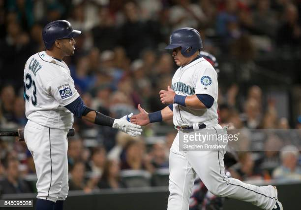 Carlos Ruiz of the Seattle Mariners is congratulated by Nelson Cruz of the Seattle Mariners after scoring on a passed ball by catcher Martin...