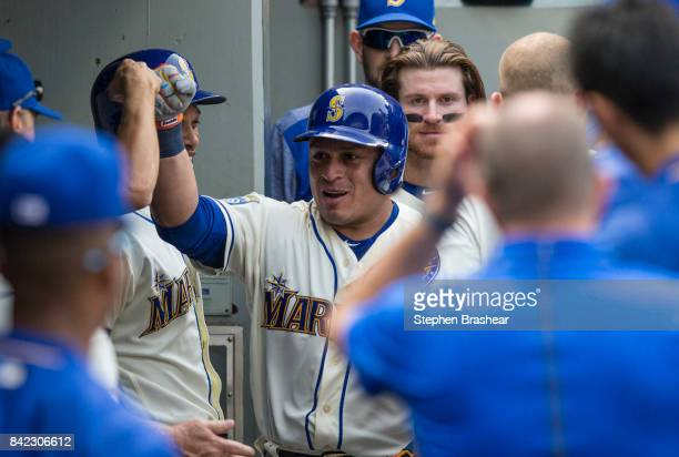Carlos Ruiz of the Seattle Mariners is congratulated by teammates in the dugout after hitting a solo home run off of relief pitcher Santiago Casilla...