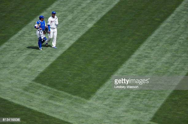 Carlos Ruiz of the Seattle Mariners left and pitcher Felix Hernandez walk to the dugout before their game against the Oakland Athletics at Safeco...