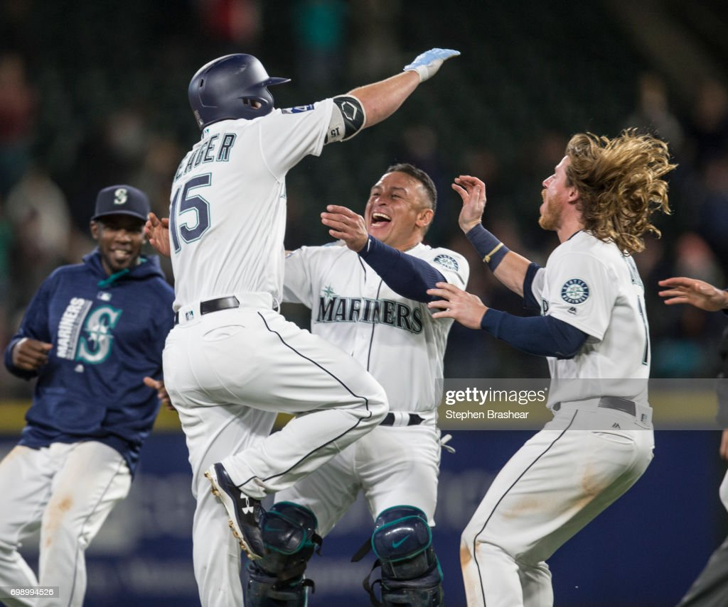 Carlos Ruiz #52, second from left, of the Seattle Mariners and Ben Gamel #16, right, of the Seattle Mariners celebrate with Kyle Seager #15 of the Seattle Mariners after Seager hit a walk off RBI-single off of relief pitcher Justin Wilson #38 of the Detroit Tigers that scored Tyler Smith #13 of the Seattle Mariners during the tenth inning of a game at Safeco Field on June 20, 2017 in Seattle, Washington.