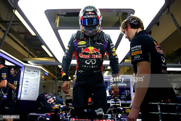 Carlos Sainz Jr of Spain and Infiniti Red Bull Racing gets into his car in the garage during day one of Formula One testing at Yas Marina Circuit on...