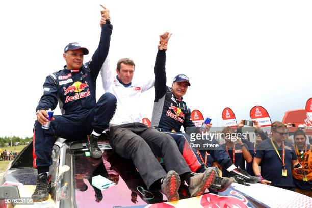 Carlos Sainz of Spain and Peugeot Total celebrates victory with codriver Lucas Cruz of Spain and Peugeot Team Manager Bruno Famin at the end of stage...