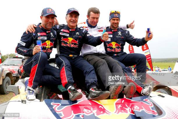 Carlos Sainz of Spain and Peugeot Total celebrates victory with teammates Stephane Peterhansel of France and Peugeot Total Cyril Despres of France...