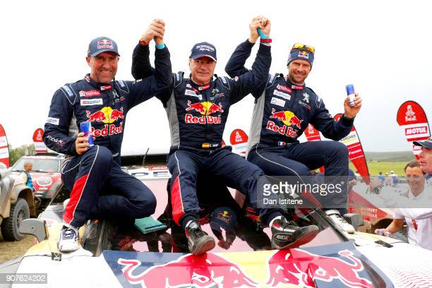 Carlos Sainz of Spain and Peugeot Total celebrates victory with teammates Stephane Peterhansel of France and Peugeot Totaland Cyril Despres of France...