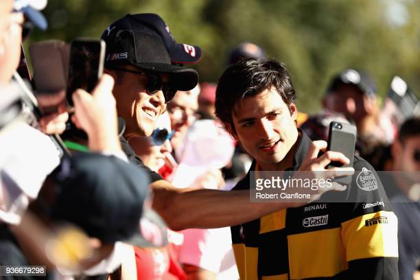 Carlos Sainz of Spain and Renault Sport F1 arrives at the circuit and poses for a photo with a fan before practice for the Australian Formula One...