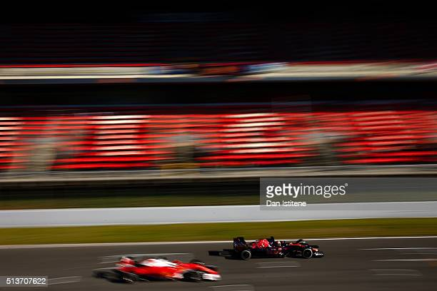 Carlos Sainz of Spain and Scuderia Toro Rosso drives ahead of Sebastian Vettel of Germany and Ferrari during day four of F1 winter testing at Circuit...