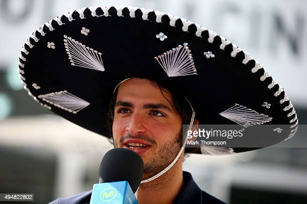 Carlos Sainz of Spain and Scuderia Toro Rosso speaks with the media wearing a sombrero in the paddock during previews to the Formula One Grand Prix...