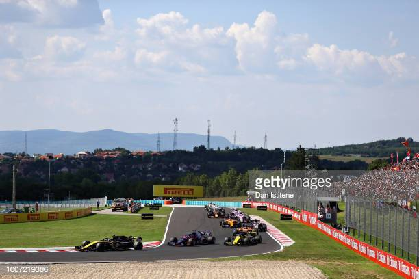 Carlos Sainz of Spain driving the Renault Sport Formula One Team RS18 leads Brendon Hartley of New Zealand driving the Scuderia Toro Rosso STR13...
