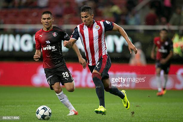 Carlos Salcedo of Chivas fights for the ball with Martin Barragan of Atlas during the 6th round match between Chivas and Atlas as part of the Torneo...