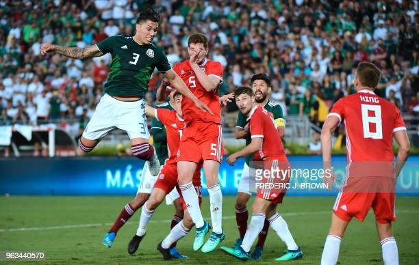 Carlos Salcedo of Mexico vies for the cross with Chris Mepham of Wales during goalmouth action in their international soccer friendly at the Rose...