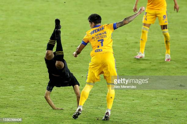 Carlos Salcedo of Tigres UANL trips up Carlos Vela of Los Angeles FC during the CONCACAF Champions League final game at Exploria Stadium on December...