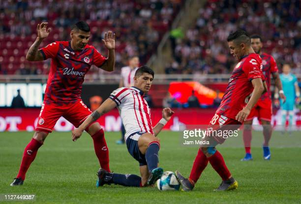 Carlos Salcido and Jesus Paganoni of Veracruz fights for the ball with Alan Pulido of Chivas during the fifth round match between Chivas and Veracruz...