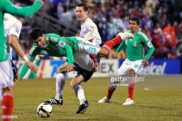 Carlos Salcido of Mexico goes airborne after being upended by Sacha Kljestan of Team USA during their FIFA World Cup qualifying match on February 11...