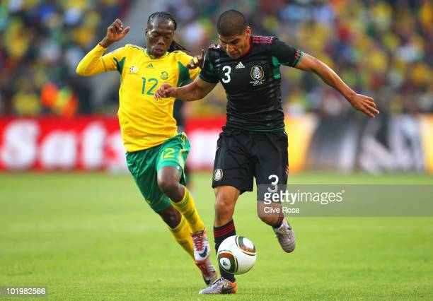 Carlos Salcido of Mexico is challenged by Reneilwe Letsholonyane of South Africa during the 2010 FIFA World Cup South Africa Group A match between...