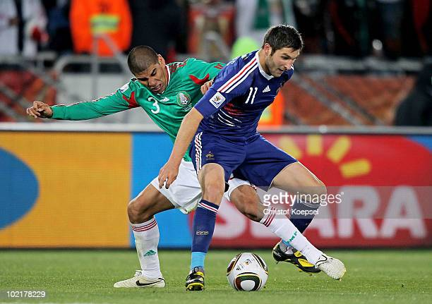 Carlos Salcido of Mexico tackles Andre Pierre Gignac of France during the 2010 FIFA World Cup South Africa Group A match between France and Mexico at...