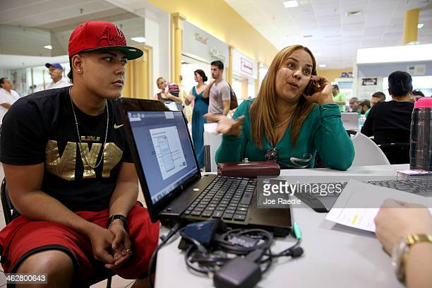 Carlos Salvador sits with his mother Yadelmis Ramirez as she speaks with an insurance agent from Sunshine Life and Health Advisors as they purchase...