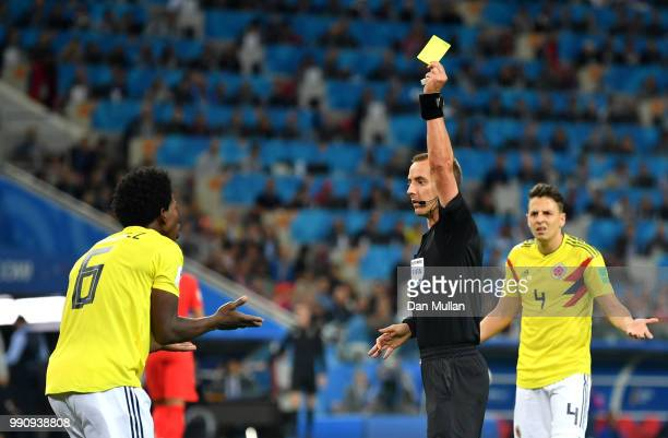 Carlos Sanchez of Colombia is shown a yellow card by referee Referee Mark Geiger during the 2018 FIFA World Cup Russia Round of 16 match between...