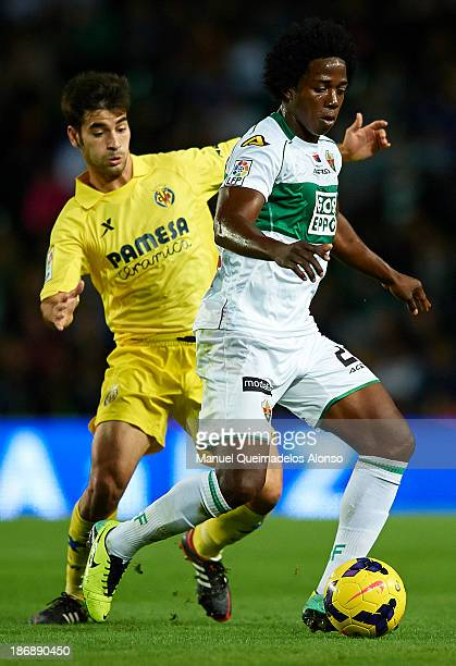 Carlos Sanchez of Elche competes for the ball with Manuel Trigueros of Villarreal during the La Liga match between Elche CF and Villarreal CF at...