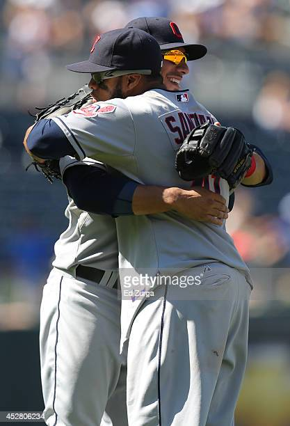 Carlos Santana and Mike Aviles of the Cleveland Indians hug as they celebrate a 103 win over the Kansas City Royals at Kauffman Stadium on July 27...