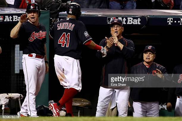 Carlos Santana of the Cleveland Indians celebrates at the dugout with manager Terry Francona after scoring a run on a wild pitch thrown by Jon Lester...