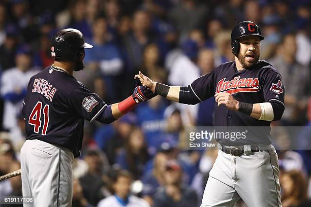 Carlos Santana of the Cleveland Indians congratulates Jason Kipnis after Kipnis scored a run in the third inning against the Chicago Cubs in Game...
